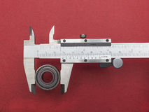 Vernier caliper with bearing. Against red background Stock Photos