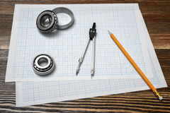 A vernier caliper holding a bearing, a pencil and a pair of compasses lying over drafting paper on wood background. Engineering and design. Repair works stock photography