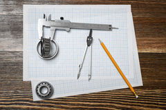 A vernier caliper holding a bearing, a pencil and a pair of compasses lying over drafting paper on wood background. Royalty Free Stock Image