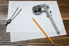 A vernier caliper holding a bearing, a pencil and a pair of compasses lying over drafting paper on wood background. Royalty Free Stock Photo