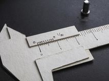 Vernier caliper made form paper. A vernier scale is a device that lets the user measure more precisely than could be done unaided when reading a uniformly Stock Images