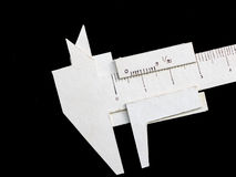 Vernier caliper made form paper. A vernier scale is a device that lets the user measure more precisely than could be done unaided when reading a uniformly Stock Photo