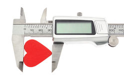 Vernier caliper measures the heart. Royalty Free Stock Photography