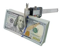 Vernier caliper and stack of $ 100 dollar bills. Isolated on white background royalty free stock photo