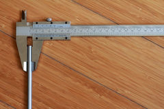 Vernier calipers. Measuring a pencil against a wooden background Royalty Free Stock Photo