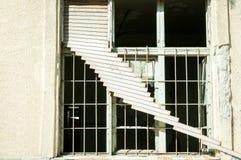 Vernietigde venster en zonneblinden van verlaten geruïneerd huis dat door granaatexplosie wordt vernietigd in de oorlogsstreek Royalty-vrije Stock Afbeeldingen