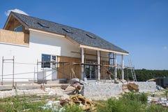 Vernieuw en herstel de woonmuur van de huisvoorgevel met gipspleister, isolatie, pleisteren, die muur schilderen De bouw van het  stock foto