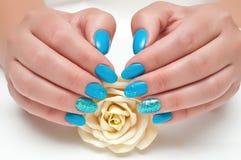 Vernis à ongles bleu avec le scintillement sur le doigt d'anneau avec une rose jaune dans sa main Photo stock