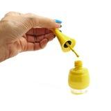 Vernis à ongles chutant de main femelle dans l'isolat de bouteille de vernis à ongles Image stock