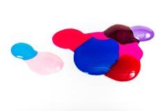 Vernis à ongles coloré renversé sur le fond blanc taches bleues et roses de peinture Images libres de droits