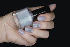 Vernis à ongles dans une main sur un fond noir Art doux de clou avec des pissenlits Photographie stock