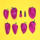 Vernis à ongles et rouge à lèvres rouges, parmi un grand nombre de poivrons rouges sur le fond jaune Images stock
