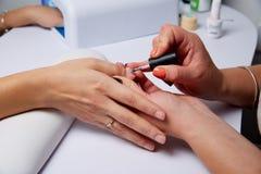 Vernis appliqué par salon de manucure sur les ongles Photographie stock