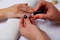 Vernis appliqué par salon de manucure sur les ongles Photo libre de droits