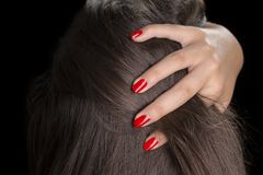 Verniz de prego vermelho que corre através do cabelo Fotografia de Stock
