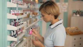 Verniz para as unhas de compra do cliente atrativo da mulher na seção da composição Menina no supermercado Fotos de Stock