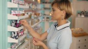 Verniz para as unhas de compra do cliente atrativo da mulher na seção da composição Menina no supermercado Foto de Stock Royalty Free