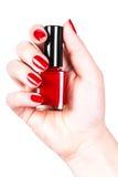 Verniz para as unhas vermelho em uma mão Fotografia de Stock Royalty Free