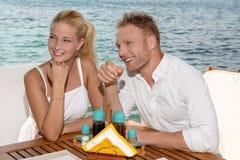 verão: pares novos que sentam-se em um restaurante ao lado do mar. Imagens de Stock