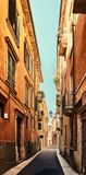 VERONA, ITALIA - 17 DE AGOSTO DE 2017: Calle estrecha de las altas fachadas vibrantes del edificio de Verona Fotografía de archivo
