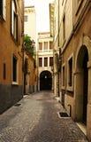 VERONA, ITALIA - 17 DE AGOSTO DE 2017: Calle estrecha de las altas fachadas vibrantes del edificio de Verona Imágenes de archivo libres de regalías