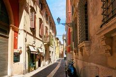 VERONA ITALIEN - AUGUSTI 17, 2017: Den smala gatan av Verona med shoppar fönster och parkering för mopeds Royaltyfria Bilder