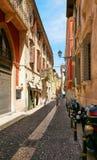 VERONA ITALIEN - AUGUSTI 17, 2017: Den smala gatan av Verona med shoppar fönster och parkering för mopeds Fotografering för Bildbyråer