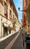 VERONA ITALIEN - AUGUSTI 17, 2017: Den smala gatan av Verona med shoppar fönster och parkering för mopeds Royaltyfri Bild