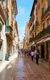 VERONA ITALIEN - AUGUSTI 17, 2017: Via Mazzini den fot- gatan med granittrottoar Shoppar och boutique Arkivbilder