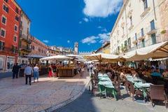 VERONA ITALIEN September 08, 2016: Köpande frukter för folk på den lokala marknaden och turister i kafét på piazzadelle Erbe Royaltyfria Bilder