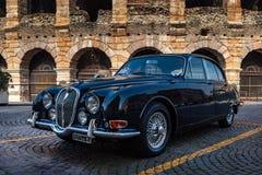 Verona, Italy – March 2019.Clasic, 1962 Jaguar Mk II | Hagerty in front of Arena di Verona an Ancient roman amphitheatre in