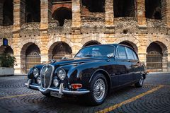 Verona, Italy – March 2019.Clasic, 1962 Jaguar Mk II | Hagerty in front of Arena di Verona an Ancient roman amphitheatre in