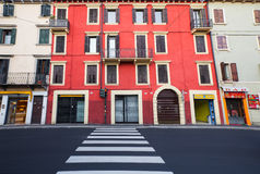 VERONA, ITALY- September 08, 2016: The crosswalk and traffic light with red light in the Verona and the narrow sidewalk of the str Royalty Free Stock Photos
