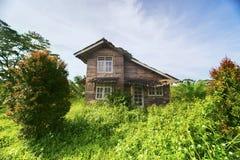 Veronachtzaamd die huis met struiken wordt overwoekerd stock fotografie