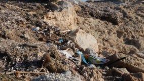Verontreinigd rotsachtig die strand met plastiek en huisvuil wordt gevuld Milieuproblemenconcept stock footage