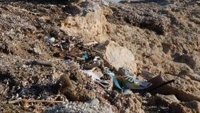 Verontreinigd rotsachtig die strand met plastiek en huisvuil wordt gevuld Milieuproblemenconcept Langzame Motie stock footage