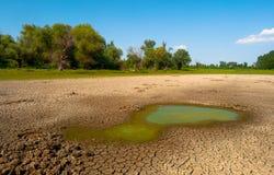 Verontreinigd water en gebarsten grond van uitgedroogd meer Stock Foto's