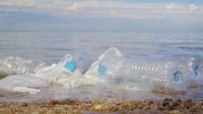 Verontreiniging: garbages, plastiek, en afval op het strand na de winteronweren stock footage