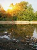 Verontreinigingsecologie huisvuil op de waterkant bij zonsondergang Royalty-vrije Stock Foto