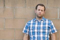 Verontruste mens die tegen een vuile concrete muur leunen Royalty-vrije Stock Foto