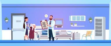 Verordnung Doktor-And Nurse Discuss für alte Frau im Krankenhaus Ward Clinic Room Interior Background Lizenzfreies Stockbild