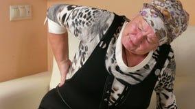 Verouderde de vrouw kan niet van de laag wegens rugpijn opstaan Zij masseert lagere achter en lijdt momenteel van stock videobeelden