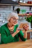 Verouderende dame die veel liefs beeldzitting bekijken bij keukenlijst royalty-vrije stock foto