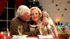 Verouderende echtgenoot die vrouw omvatten met comfortabele plaid en haar koesteren teder, Kerstmisvooravond royalty-vrije stock afbeelding