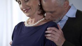 Verouderende echtgenoot kussende dame in parels op schouder, speciale gelegenheid, geluk stock afbeelding