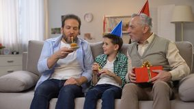 Verouderende mannetje en schooljongen die de mens op middelbare leeftijd met giftdoos en cake gelukwensen stock footage