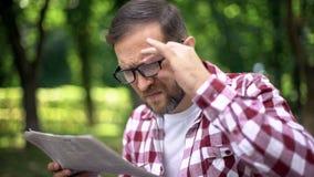 Verouderende mens in oogglazen die krant in park, verziendheid, bijziendheid proberen te lezen stock foto's