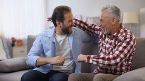 Verouderende vader en midden oude de vuisten vriendschappelijke gezinsverhoudingen van het zoonsponsen, vertrouwen stock video