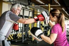 Verpacken des älteren Mannes in der Turnhalle Älterer Mann mit persönlichem Trainer stockfotos
