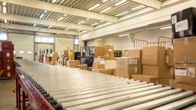 Verpacken Sie Kästen für Lieferung im DHL-Lagerhaus Stockfoto